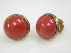 Coral Studs  Product Information  One pair of 18 karat yellow gold stud earrings set with two round cabochon coral.   Price: $2800.00