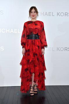 Dakota Johnson con vestido rojo con estampado floral, bajo asimétrico y cinturón ancho de cuero negro, de la colección Primavera 2016 de Michael Kors.