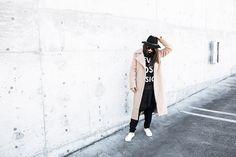 Shop this look on Lookastic:  http://lookastic.com/women/looks/hat-crew-neck-sweater-sweatpants-slip-on-sneakers-coat/8468  — Black Wool Hat  — Black and White Print Crew-neck Sweater  — Black Sweatpants  — White Leather Slip-on Sneakers  — Beige Coat