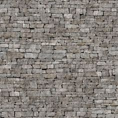 Stacked grey stone wall. Looks like the side of a castle.