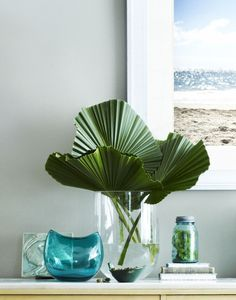 Large-scale leaves—like philodendrons, birds of paradise and palm fronds—can double as sculpture. Corral a few leaves in a tall vase on a sideboard, or highlight just one in a narrow vase on a nightstand or shelf.