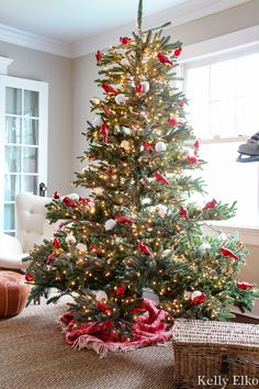 WOW love this realistic looking sparse Christmas tree filled with red carinal ornaments kellyelko.com #sparsechristmastree #realisticchristmastree #vintagechristmas #christmastree #christmasornaments #rattanfurniture #daybed #cozychristmas #farmhousechristmas #treeskirt