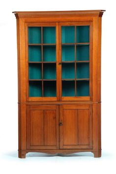 """ONE-PIECE SIXTEEN-PANE CORNER CUPBOARD. American, mid 19th century, walnut with pine secondary. Molded cornice, two single panel lower doors and cutout apron. 84""""h. 53""""w. 24""""d. Takes a 36"""" corner."""