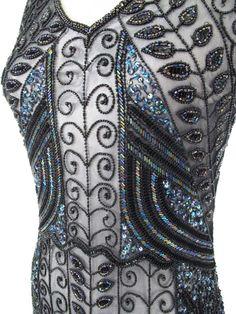 <p>1920s reproduction Marcelle black beaded flapper dress radiates deco decadence! The intricate hand loomed beadwork is amazing, just like the originals from the era of smoky jazz clubs and silent film sirens. Perfect for art deco or Gatsby themed events or a night out dancing at an upscale nightclub! <br /><br />•V neckline. <br />•Scalloped hem. <br />•Pull on style. <br />•Black and rainbow iridescent beading and sequins on a fine mesh ground. <br />•Two rows of ...