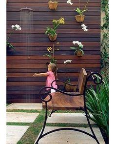 A pequena Sophia sempre deixa a sua brinquedoteca para curtir o jardim. Ao fundo, as orquídeas dão cor ao painel vertical de madeira, que recebeu um chuveirão para refrescar as crianças nos dias de calor. Projeto da paisagista Irene Cisneros . (Foto: Evelyn Müller e Tatiana Villa/Casa e Jardim) #decor #paisagismo #fresh #summer #verão2017 #vemverao