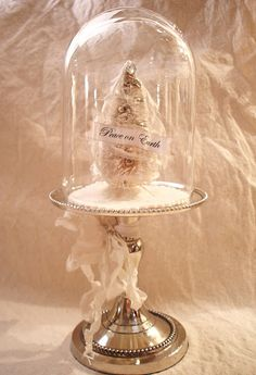 White bottle brush tree under a cloche - love the silver cake stand