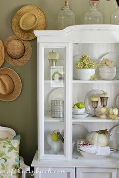 Gorgeous Fall Hutch decor. Beautiful crisp white hutch against sage green walls and a straw hat display.