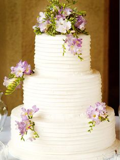 Cake decorating can be as simple as artfully placing a handful of your favorite flowers around the tiers of your confectionary delight. Here, a few sprigs of lavender freesia decorate the three-tier cake.
