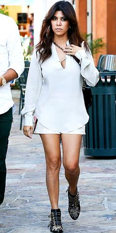 """Kourtney Kardashian in white top and shorts with studded black Chloe """"Susanna"""" boots."""