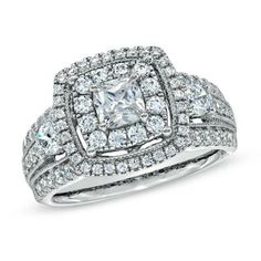 This glistening gem is wrapped in a double border of shimmering round accent diamonds, which carry through to the wide split shank.