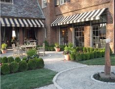 boxwood lining an outdoor dining area- striped awnings over doorways n windows