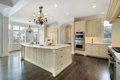 Very light wood (soft yellow) kitchen design with white ceiling and dark wood flooring.