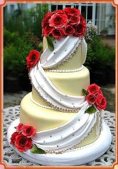 Floral Cake  A wedding cake with red flowers and white draping.