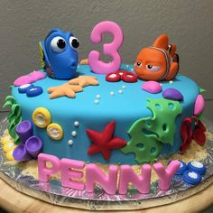 Nemo and Dorys Cake for a 3 year old girl. We made the number and name in pink to make this cake more girly. #nemo #dory #cake Follow us on instagram and Facebook @arlyscakes www.arlyscakes.com