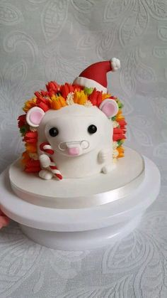 Cute hedgehog cake with fondant christmas hat and candy cane. Tutorial on website. An original Little Peach Cakery cake design