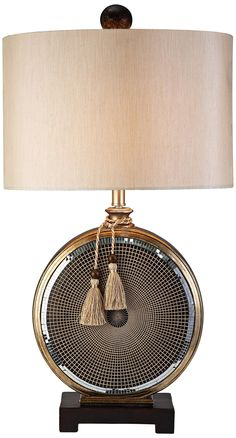Brighten a bedroom or living space with the Mosaic Table Lamp. Featuring a beige drum shade and gold mosaic base, this lamp is eye-catching and chic. Display it among elements of contemporary decor as a unique accent piece.