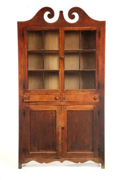 """CUPBOARD -    American, 19th century, walnut and poplar. One piece, the upper section with a broken-arch pediment over two 6-pane doors; the lower section with two drawers over two doors, all on a shaped base. Retains a good old surface. 83.5""""h. 45""""w. 13""""d."""