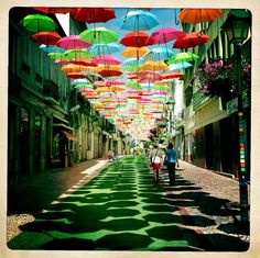 In Águeda, a small Portuguese town, some streets are decorated with colorful umbrellas. The umbrellas cover heads from the hot summer sun.