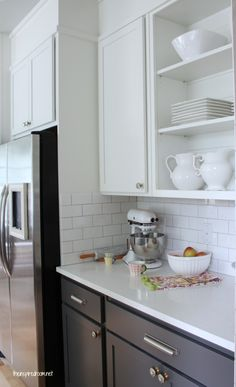 White top cabinets and dark gray bottom ones with subway tile backsplash.