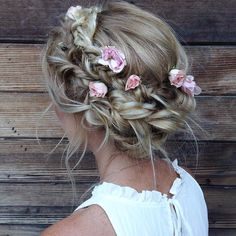 Stunning and stellar. Add flowers to your braided halo for a romantic and soft style #weddinghair