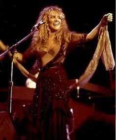 Stevie laughing onstage, wearing varying shades of brown over a pale brown body suit  ~ ☆♥❤♥☆ ~    love her hair and her glittery scarf