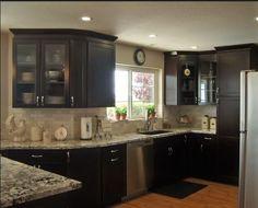 Granite + backsplash kitchen idea love the glass cabinet door and the dark color