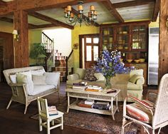 Casual elegence caputured by the worn white whicker furniture, post and beam ceiling and heirloom oriental rug in this summer home living room