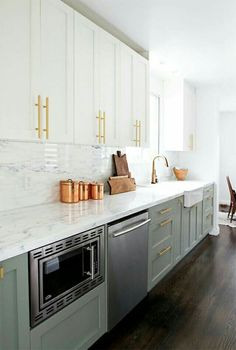 modern kitchen design. white cabinets on top, grey cabinets on bottom. with brass hardware and marble countertops