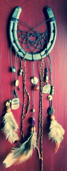 Dream catcher made out of horse shoe with pebbles, beads and feathers.