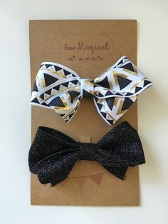 $4.75 Set of 2 Clip in hair bows. One tribal print gold, white, and black and one black glitter clip. Hair clip measures at 3inches. Lined with ribbon to