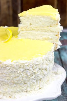 Lemon coconut Cake...Decadent coconut flakes...sweet vanilla buttercream...tart lemon curd. One slice of this Lemon Coconut Cake will whisk you away to a warm Caribbean island!