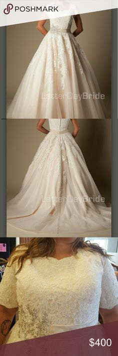 Latter-Day Bride Wedding Dress This lovely modest bridal gown features a delicate sweetheart neckline with scalloped lace, a flattering bedazzled belt at the natural waist and cascading lace detail throughout the full A-line skirt.  Dress is Ivory with some light blush pink tulle 3 layers down. Latter-Day Bride Dresses Wedding