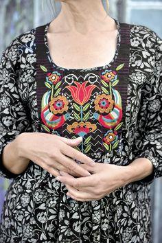 """Das schwarze Öko-Baumwollkleid """"Hanna"""" hat eine reich bestickte Brustpasse. Die Falten auf der Vorderseite bewirken eine großzügige Passform um die Hüfte herum."""