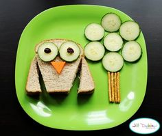 Owl sandwich - brown bread sandwich with favorite filling, cucumber eyes and tree, raisin eyes, cheese nose, pretzel tree trunk