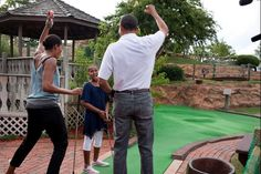 President Barack Obama and First Lady Michelle Obama react to daughter Sasha's hole in one while playing miniature golf at Pirate's Island Golf in Panama City Beach, Fla., Saturday, Aug. 14, 2010.