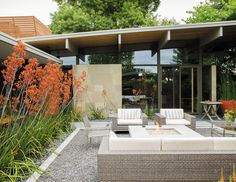 Behind the resin screen is the property's centerpiece: an entry garden that Trainor recast as an outdoor living room. Sparta stacking chairs, a deep-wicker Baia sofa, and matching Baia armchairs, all by Mamagreen, are arranged around a custom concrete fire pit. Orange kangaroo paws lean in from the sides, creating a sense of privacy without sacrificing views. It's a welcoming space that serves as a casual gathering spot when the weather cooperates.