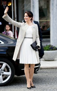 Crown Princess Mary of Denmark wears a white flowy dress, ivory coat, black pointed toe pumps, black clutch and black hat.