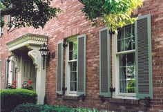 Full Louvered shutters on a brick dwelling create a classic style.