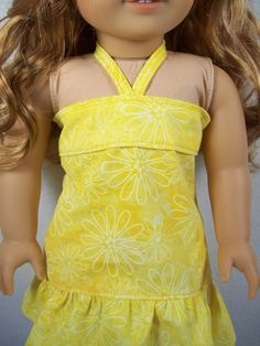 This bright yellow sundress is the perfect dress for those hot summer days. The dress is made with yellow cotton material with a floral pattern. It has a ruffled hem and closes in the back with Velcro and ties at the neck.  This dress is made to fit 18 dolls, such as American Girl®.  All of my doll clothes are made with new materials in a smoke-free home. Material design placement may vary slightly from the picture.  American Girl® is a trademark of American Girl, LLC. Our Doll Fashions is…