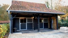 Outdoor stable block with large roof overhang.
