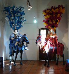 Caballeros Medievales con Armadura y Ornamentos - Caballeros montados con sus respectivas armaduras, yelmos y caballos totalmente ataviados para desfiles especiales. Se destaca la complejidad de sus uniformes, el peso de sus ornamentos y la fastuosidad de sus plumas sobre la cabeza.