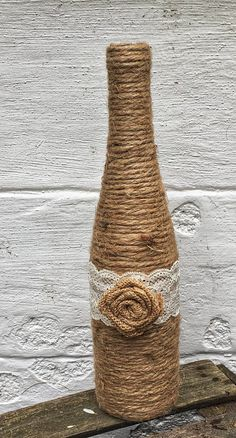 Twine Wrapped Wine Bottles are a great addition to your Country Themed event! These upcycled wine bottles are decorated simply and rustically with twine! Each bottle is then embellished with a handmade burlap rose and lace to add an extra touch to your party decor! These Country Chic