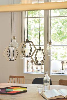 Lámpara colgante compuesta sobre mesa de comedor y bandejas geométricas de…