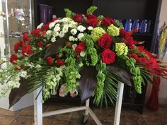 Red roses, red gladiolus, red mini carnations, mini green hydrangeas & bells of Ireland casket spray by Donna Jeffries
