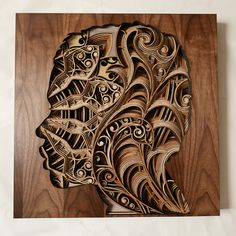 Oakland-based artist Gabriel Schama (previously) continues to produce intricate relief sculptures by layering pieces of laser-cut mahogany plywood. Some of his most impressive new works see mandala-like shapes contained within the silhouettes of people's faces, a striking idea that imbues e