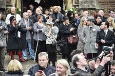 Mourners - some dressed in bright, patterened outfits - gathered outside All Saints Church...