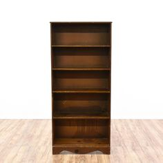 This tall bookcase is featured in a solid wood with a dark oak wood finish. This bookshelf is in good condition with 4 shelf tiers and curved base trim. Simple storage piece perfect for displaying books and knick knacks! #americantraditional #storage #bookcase&shelving #sandiegovintage #vintagefurniture