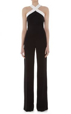 Roland Mouret fuses formality with soft draping on the elegant Shotwick Jumpsuit. This solid black ensemble is contrasted with a white cross over halter neck and a strappy back of broad, skin-flashing bands. A wide pant leg and draped folds at the bodice add easy-going glamour.