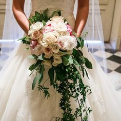 Dana carried a beautiful cascading rose bouquet with pale pink and white roses and peonies. Green leaves and vines hung below the bouquet.