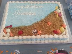 Beach themed graduation cake, made with buttercream icing, the sand is brown sugar the sea life is white chocolate (and food coloring to look real) made by The Sweet Chef
